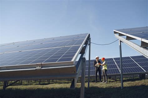 Engineer interacting with colleague standing near solar